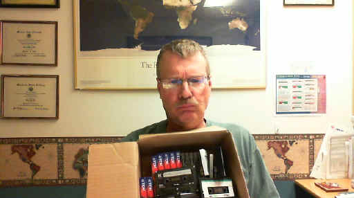 Unhappy frowning Pat with cardboard box of assorted tape cassettes.