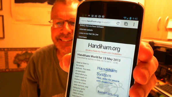 Pat holds Nexus 4 smartphone up for camera to show mobile Handiham.org website.