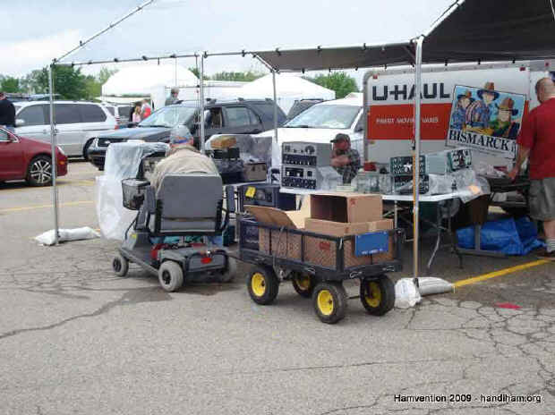 Guy driving scooter with wagon of Hamvention treasures in tow