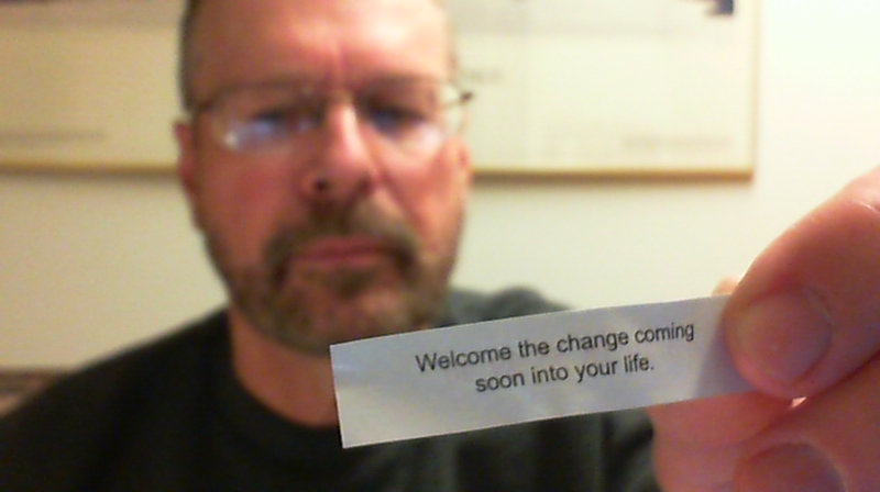 "Pat, blurred in background, holding fortune from fotune cookie, stating, ""Welcome the change coming soon into your life."""
