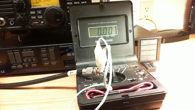 Digital multimeter, coaxial jumper to be tested, and clip lead.