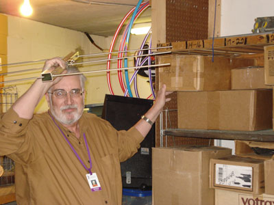 George, N0SBU, finds room for an antenna in the storeroom following radio camp.