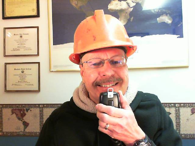 Pat, WA0TDA, wearing orange hard hat, talking into microphone.