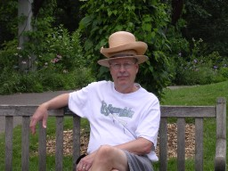Pat sitting on bench, wearing stacked straw summer hats