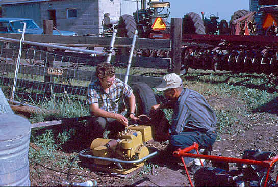 Pat, WA0TDA, (L) and Newt Owens, owner of the farm, gas up the generator in this old Field Day photo from the 1970's.