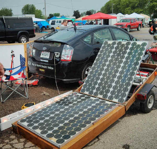 Prius with trailer in foreground showing banks of solar cells that can be pulled along behind while driving down the road. The car itself has two banks of solar cells, one on the roof and the other on the hood.