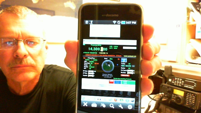 Pat, wa0tda, holds smartphone that controls radio in the background of the photo.