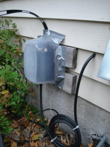The plastic food container covers the MFJ current balun at the point of entry outside the ham shack.