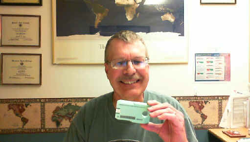 Smiling Pat holds up a single Library of Congress digital cartridge.  The small green cartridge is not quite as large as a single 4-track cassette tape.