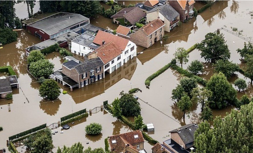 Photo of damaged buildings with floodwaters surrounding them.