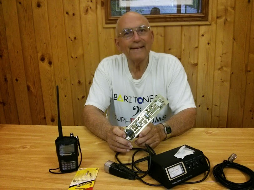 Photo of Bill sitting at a table with several amateur radio teaching aids.