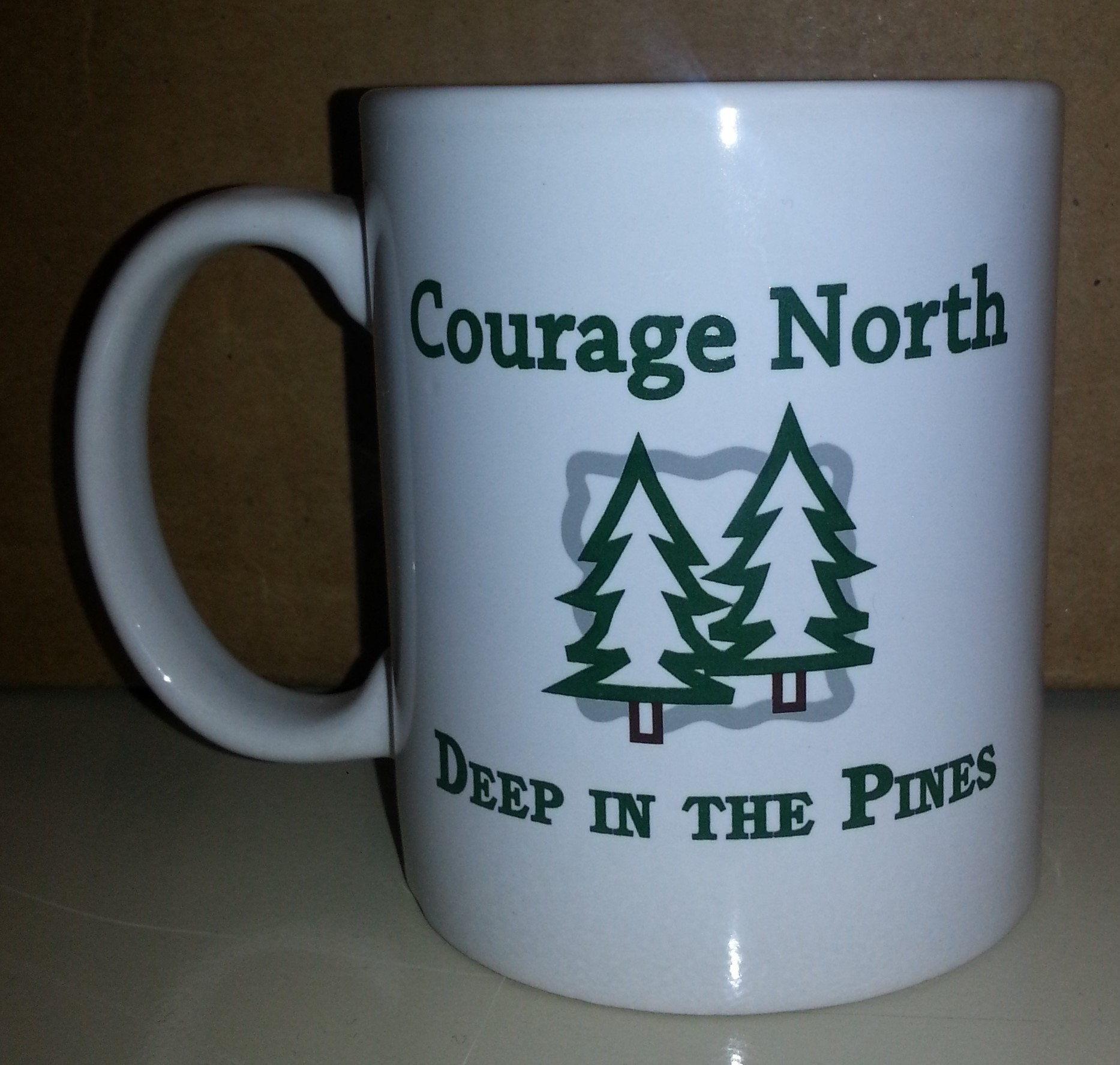 "White mug Courage North Deep in the Pines printed in green on the front"" width="