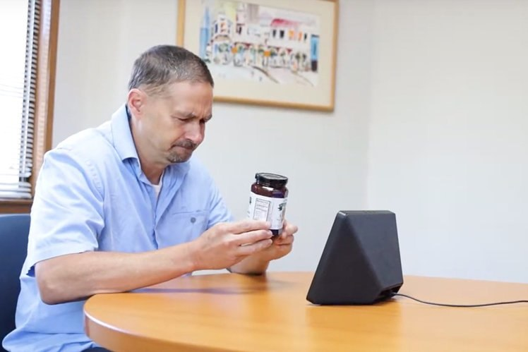 photo of blind person holding a package of food in front of the camera on the Echo Show