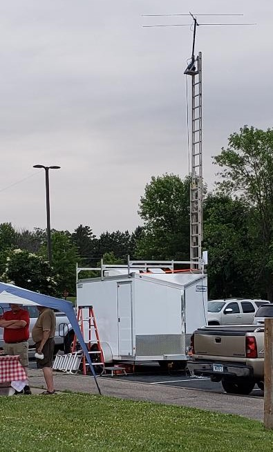 photo of communications trailer with beam antenna located at the top of an extended ladder lashed to the trailer.