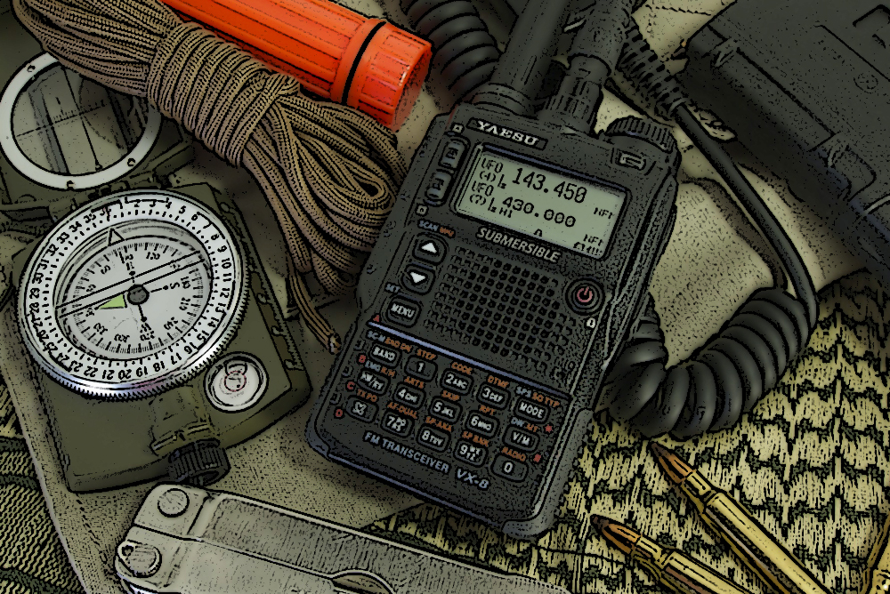 Photo of Yaesu handheld radio along with other survival gear including a rope, compass, and knife.