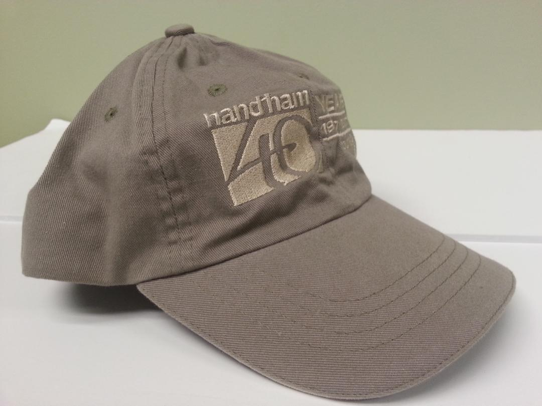 "Tan baseball cap with with Handiham 40th Anniversary logo embroidered on the front"" width="