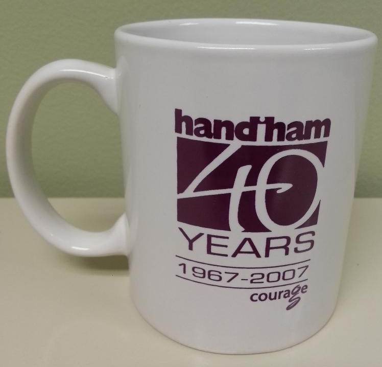 "White mug with Handiham 40th Anniversary logo printed on the front and back"" width="