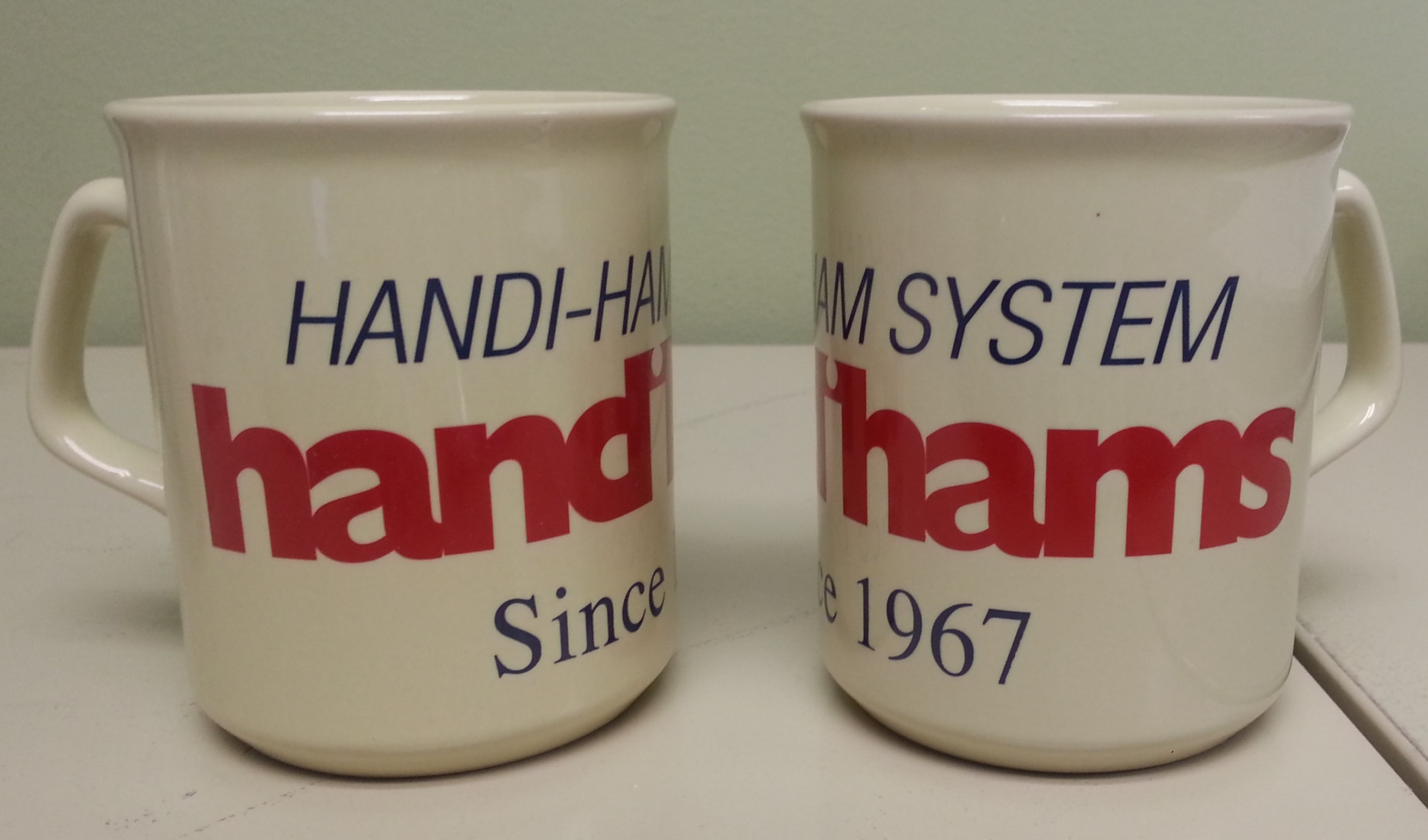 "Cream-colored mug with Handiham System Handihams since 1967 printed in blue and red on the front"" width="