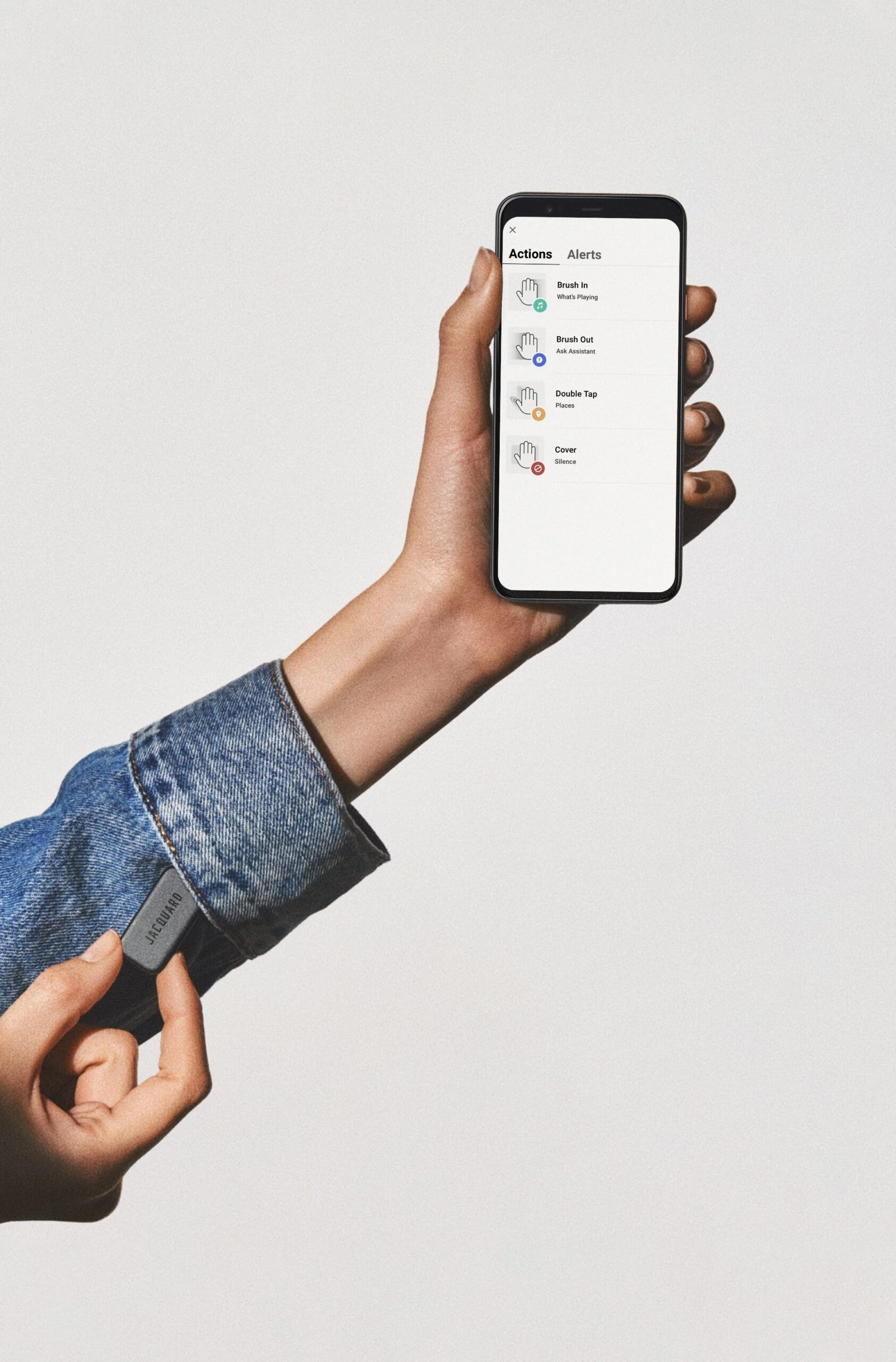 Photo of Jaquard assistive technology device being held next to an insertion point in a jacket cuff; another hand holds a smartphone.