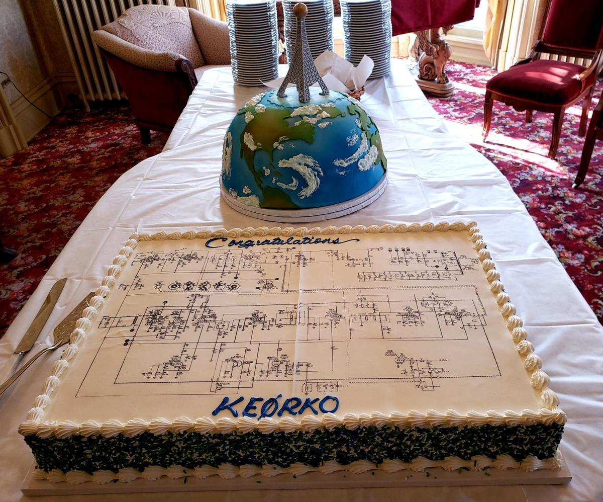 photo of two amateur radio themed cakes, one with a schematic diagram and the other of the world with an antenna tower on top.