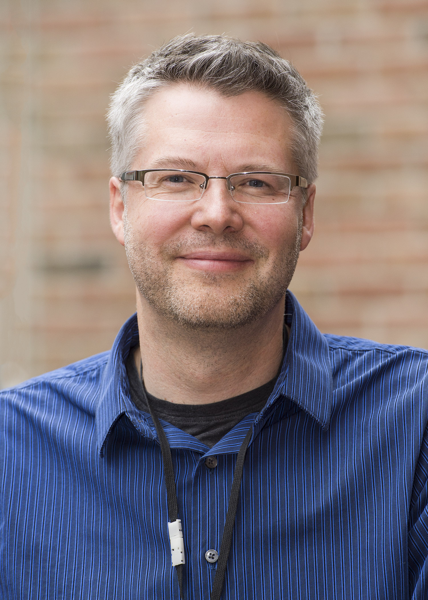 "Photo of a smiling Matt White wearing glasses and a blue striped shirt"" width="