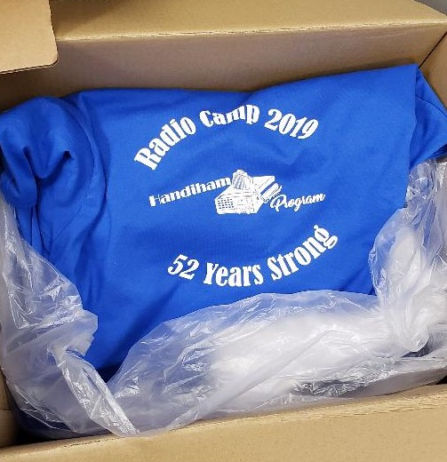 photo of open box with blue Handiham Program Radio Camp T-shirts inside