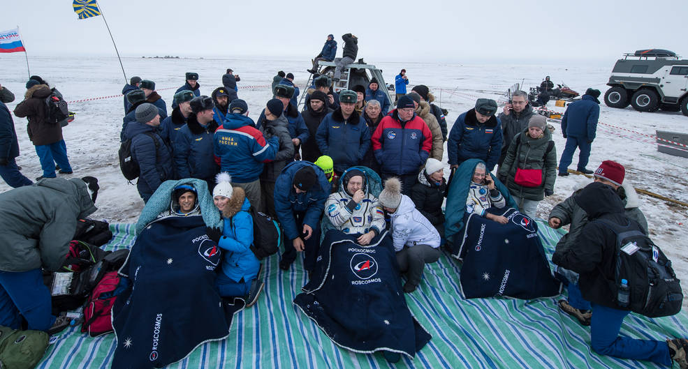 "The astronauts, reclining and covered in blankets, smiling with loved-ones as medics check them out after landing in their Soyus spacecraft."" width="