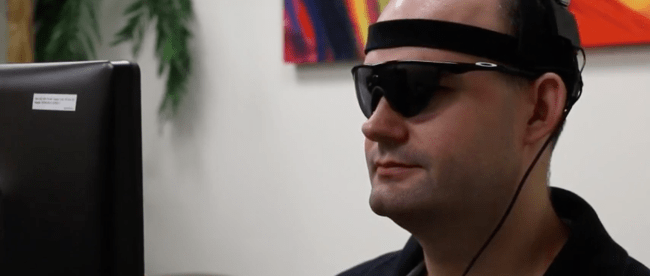 photo of person wearing sunglasses with camera that sends the information to be transmitted to the Orion brain implant