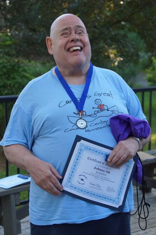 photo of Johnny, WA8WFH, with his certificate and medal