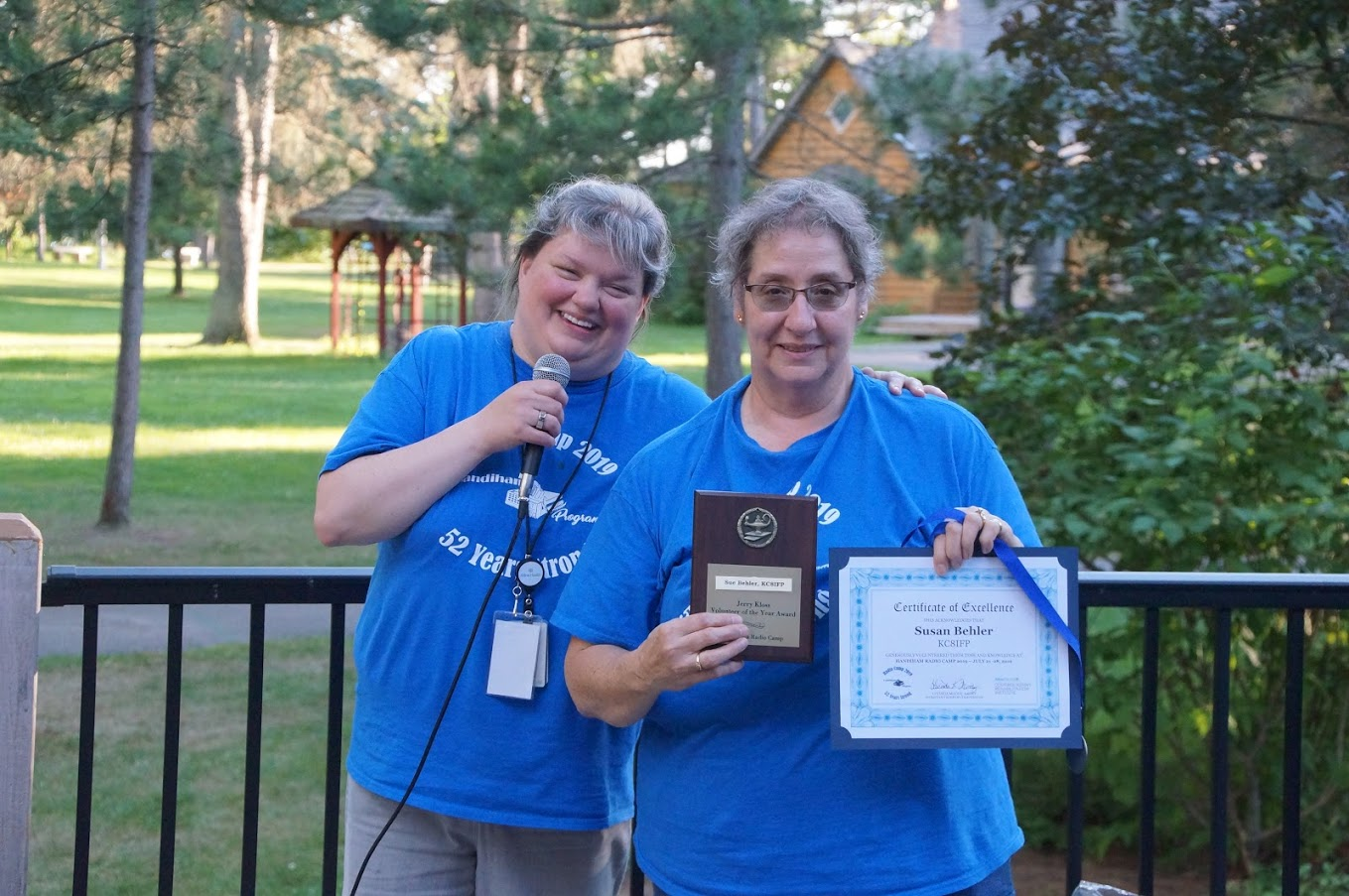photo of Sue Behler receiving her Jerry Kloss Volunteer of the Year Award, certificate, and medal