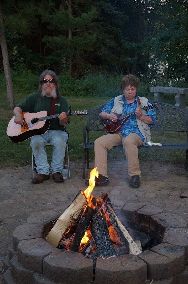 photo of Matt and Lynelle playing instruments and singing by the campfire