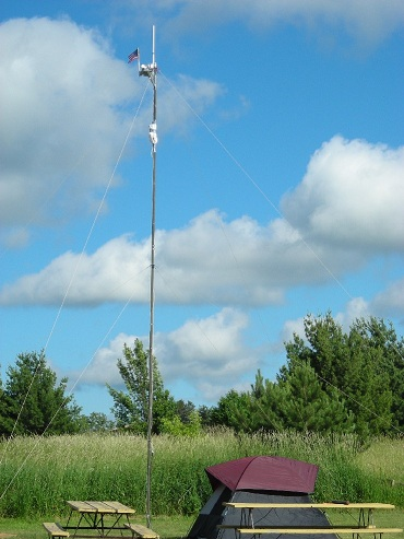 Vertical antenna with small American flag on top at Field Day site with tent and picnic table in foreground.