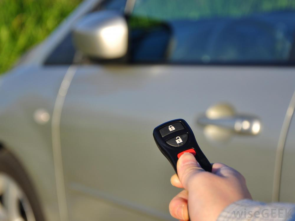 Photo of person using a keyless entry device with a car in the background.