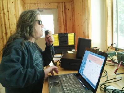 "Matt, KA0PQW, at the Handiham Radio Camp in 2013.  He is sitting at a desk operating a Kenwood 590 radio using a handheld microphone"" width="