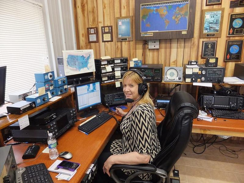 "Valerie, NV9L, sitting at the operating position in her ham shack that has numerous awards posted on the wall."" width="