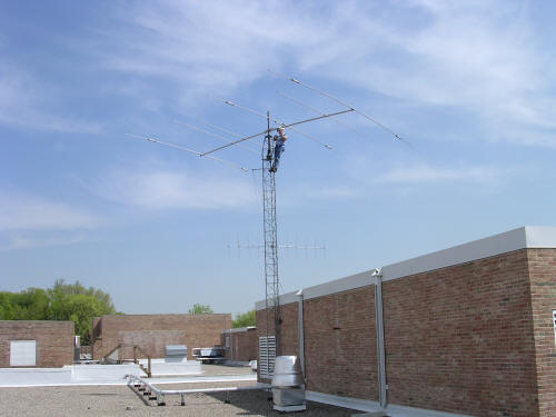 Worker on tower fixing triband beam antenna